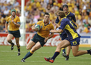 Brisbane, October 18, 2003. Matthew Burke on the weave before scoring a try in the first half of the Australia v Romania Rugby World Cup Pool A match at Suncorp Stadium, Brisbane. AAP Image/Dave Hunt