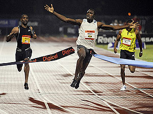 Jamaica's Usain Bolt, center, breaks the tape with a world record time of 9.72 seconds in the men's 100 meter sprint at the Reebok Grand Prix athletic meet at Icahn Stadium in New York. AP Photo/Bill Kostroun