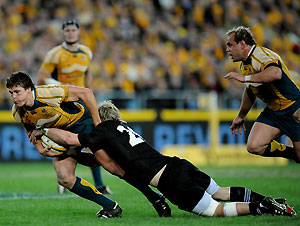 Australian rugby union player Luke Burgess is tackled by Jimmy Cowan from New Zealand in the first match of the Bledisloe Cup series in Sydney on Saturday, July 26, 2008. The Wallabies beat the All Blacks 34-19. AAP Image/Paul Miller