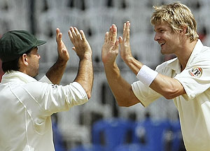 Australian cricket captain Ricky Ponting, left, runs-in to congratulate bowler Shane Watson after he took he wicket of Indian captain Anil Kumble, unseen, on the fourth day of their first test in Bangalore, India, Sunday, Oct. 12, 2008. (AP Photo/Gautam Singh)