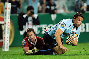 The Waratahs' Timana Tahu runs in to score as he's tackled by the Reds' Mark McLinden during their Super 14 match at the Sydney Football Stadium, Sydney, Friday, March 6, 2009. AAP Image/Dean Lewins