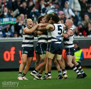 Geelong players mob Jimmy Bartel after his scores a point to win the game during the AFL Round 17 match between the Geelong Cats and the Hawthorn Hawks at the MCG.