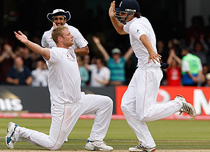 England's Andrew Flintoff, on his knees, is congratulated by teammates after bowling the wicket of Australia's Peter Siddle. AAP Images