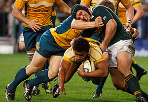 South Africa's Victor Matfield, right, tackles Australia Will Genia, center, during their Tri Nations rugby match in Cape Town, South Africa, Saturday, Aug. 8, 2009. (AP Photo/Schalk van Zuydam)