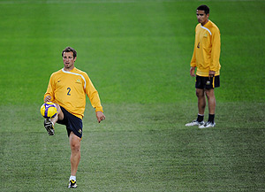 Socceroo Tim Cahill (r) watches as Lucas Neill kicks the ball during a team training session ahead of tomorrow's World Cup qualifying match against Bahrain in Sydney on Tuesday, June 9, 2009. Australia qualified for the 2010 World Cup in South Africa with a 0-0 draw against Qatar last Saturday. AAP Image/Paul Miller