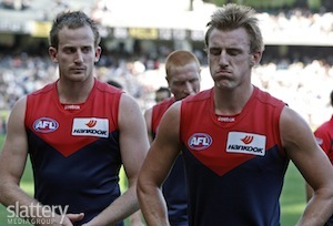 Melbourne's Michael Newton and Lynden Dunn look dejected at the finish of the AFL Round 02 match between the Collingwood Magpies and the Melbourne Demons at the MCG, Melbourne.