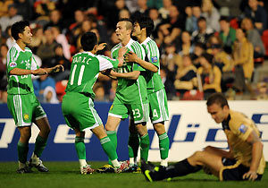 Beijing Guoan's Ryan Griffiths (centre) is surrounded by his team-mates. AAP Image/Paul Miller