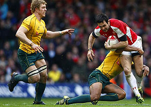 Wallabies' David Pocock watches as Wales' Stephen Jones is tackled against Australia. AP Photo/Tim Hales