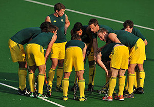 The Australian men's hockey team group into a huddle before taking a penalty corner
