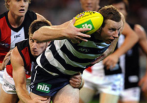 Steven Johnson of Geelong is tackled by St Kilda's Andrew McQualter. AAP Image/Joe Castro