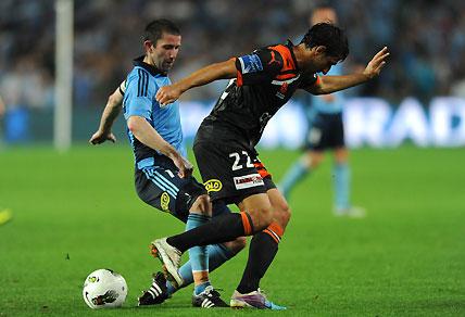 Sydney FC's Terry McFlynn tackles the Brisbane Roar's Thomas Broich.