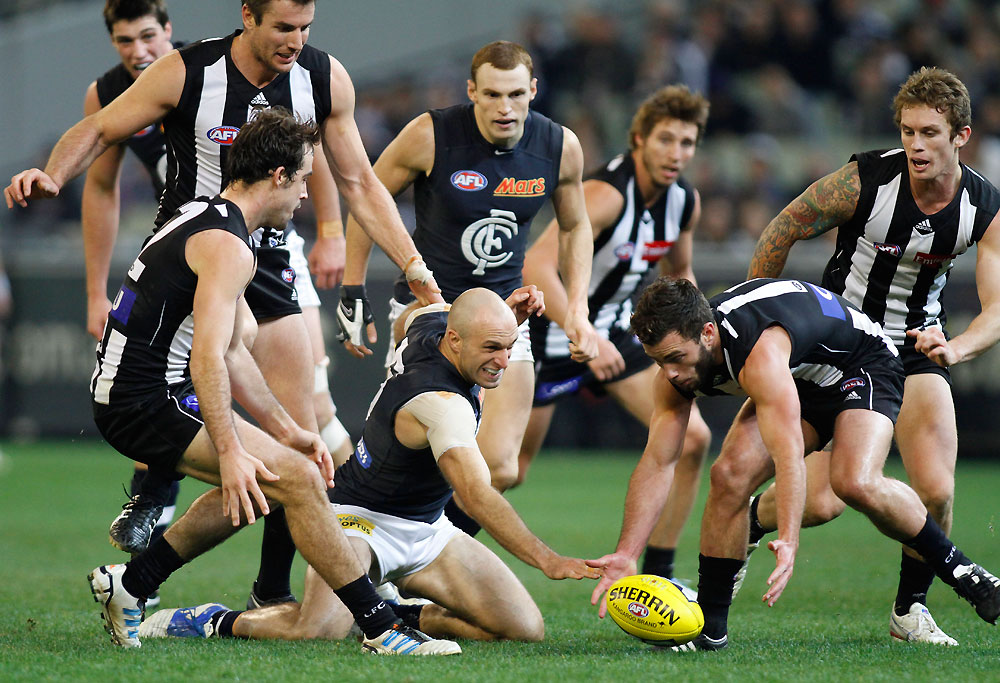 Collingwood's Jarryd Blair and Carlton's Chris Judd contest for the ball in a pack of players