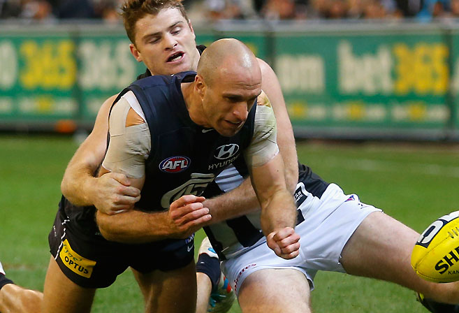 Carlton's Chris Judd is tackled by Collingwood's Heath Shaw
