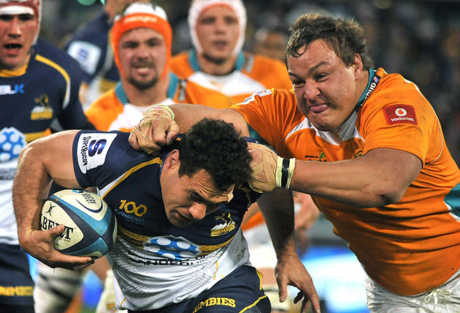 Coenie Oosthuizen (R) of the Cheetahs tackles Brumbie George Smith. AFP PHOTO / Mark GRAHAM