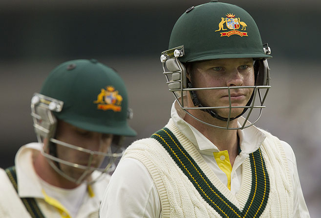 Australia's Steve Smith, right, and Phillip Hughes walk from the pitch at stumps after the first day of the opening Ashes series cricket match. (AP Photo/Jon Super)
