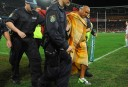 A streaker is escorted off the field during State of Origin Game 3 (AAP Image/Dean Lewins)