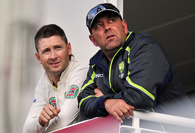 Michael Clarke and Darren Lehmann ponder Australia's fortunes during the fifth Ashes Test at The Oval (AFP PHOTO / GLYN KIRK).