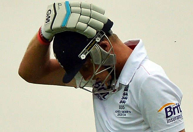 England's batsman Joe Root holds his head as he walks back to pavilion