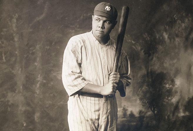 Babe Ruth, full-length portrait, standing, facing slightly right, in baseball uniform, holding baseball bat.
