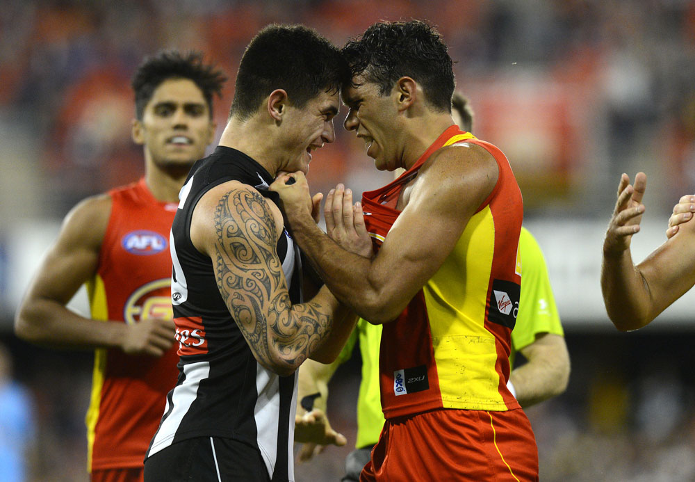 Magpies player Marley Williams (left) and Suns player Harley Bennell. (AAP Image/Dave Hunt)