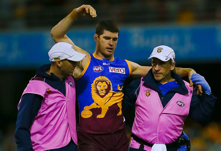 Brisbane Lions player Jonathan Brown is assisted from the field