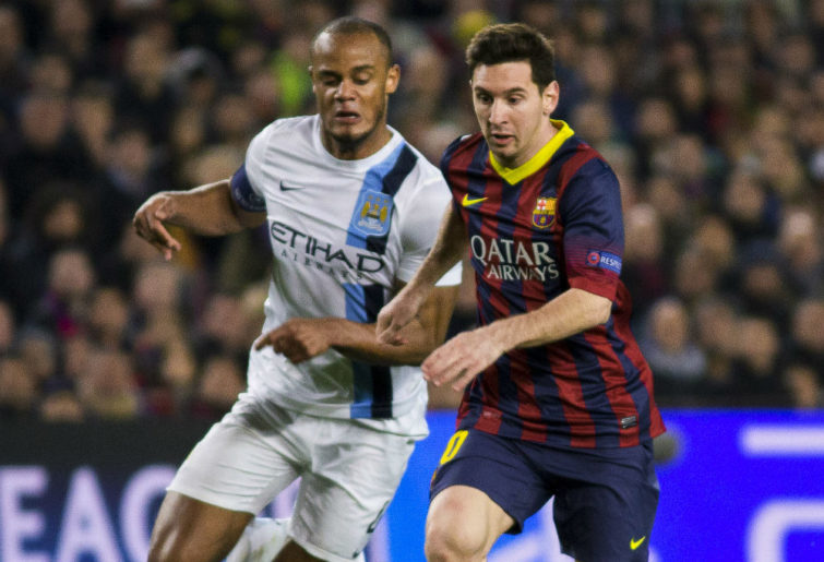 Vincent Kompany and Lionel Messi compete for the ball
