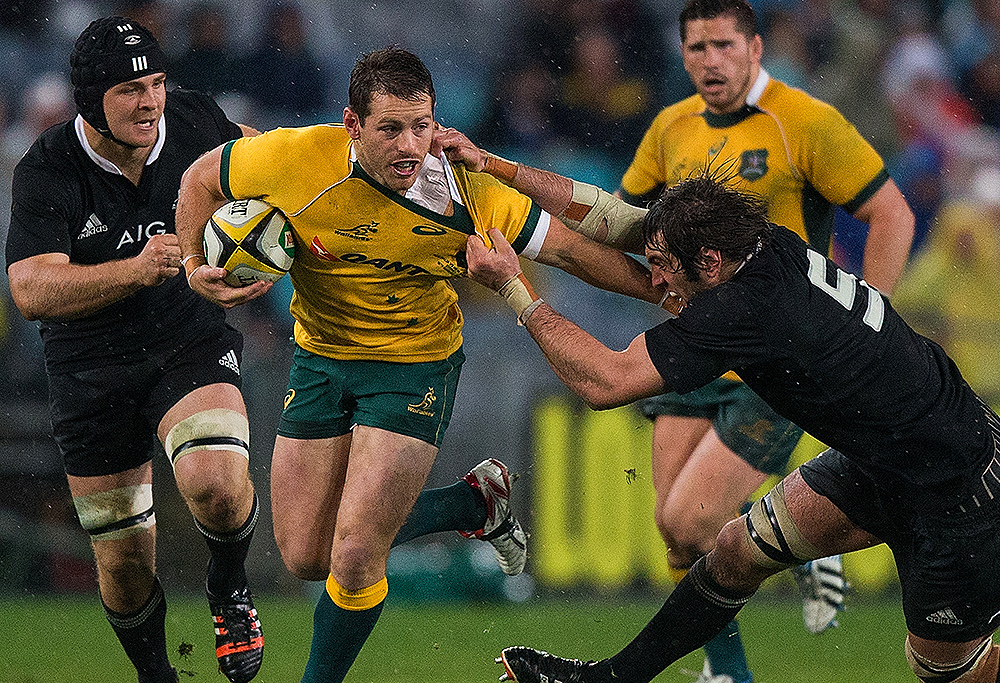 Bernard Foley of the Wallabies is tackled by Samuel Whitelock of the All Blacks during the opening game of the Bledisloe Cup series between the Wallabies and the All Blacks at ANZ Stadium in Sydney, Saturday, Aug. 16, 2014. (AAP Image/Joosep Martinson)
