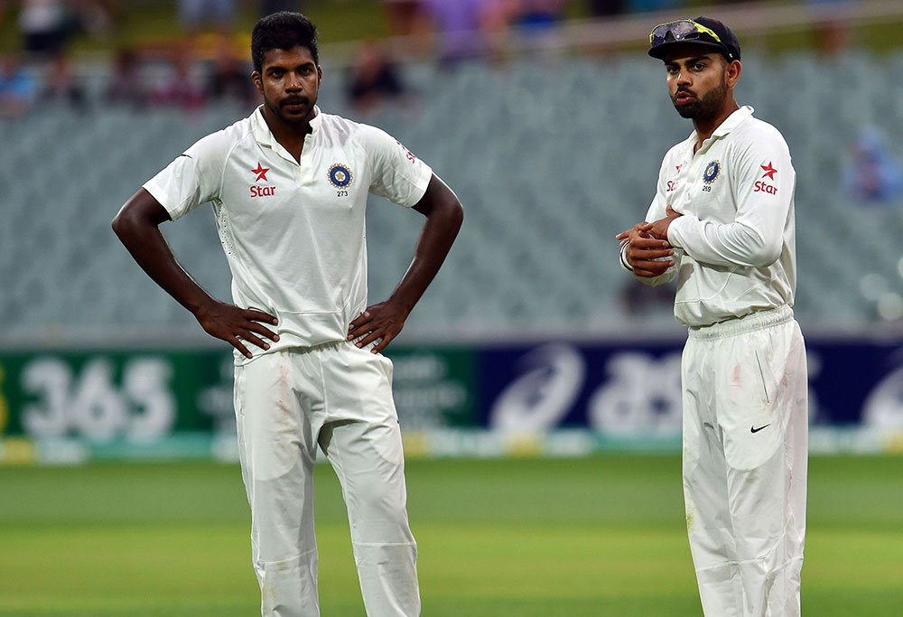 India's captain Virat Kohli (R) gives instructions to his pacer Varun Aaron