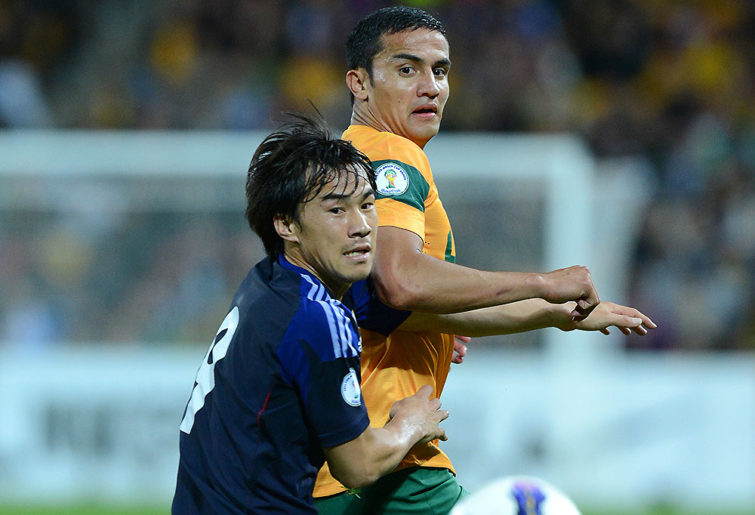 Shinji Okazaki competes with Socceroos player Tim Cahill