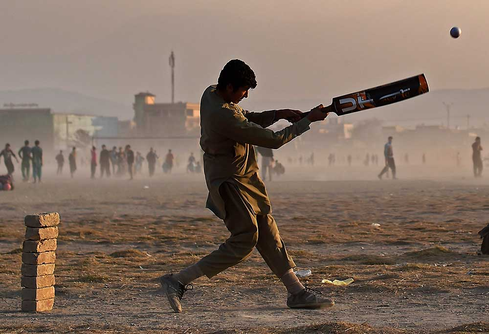 Boy playing cricket in war-torn Afghanistan