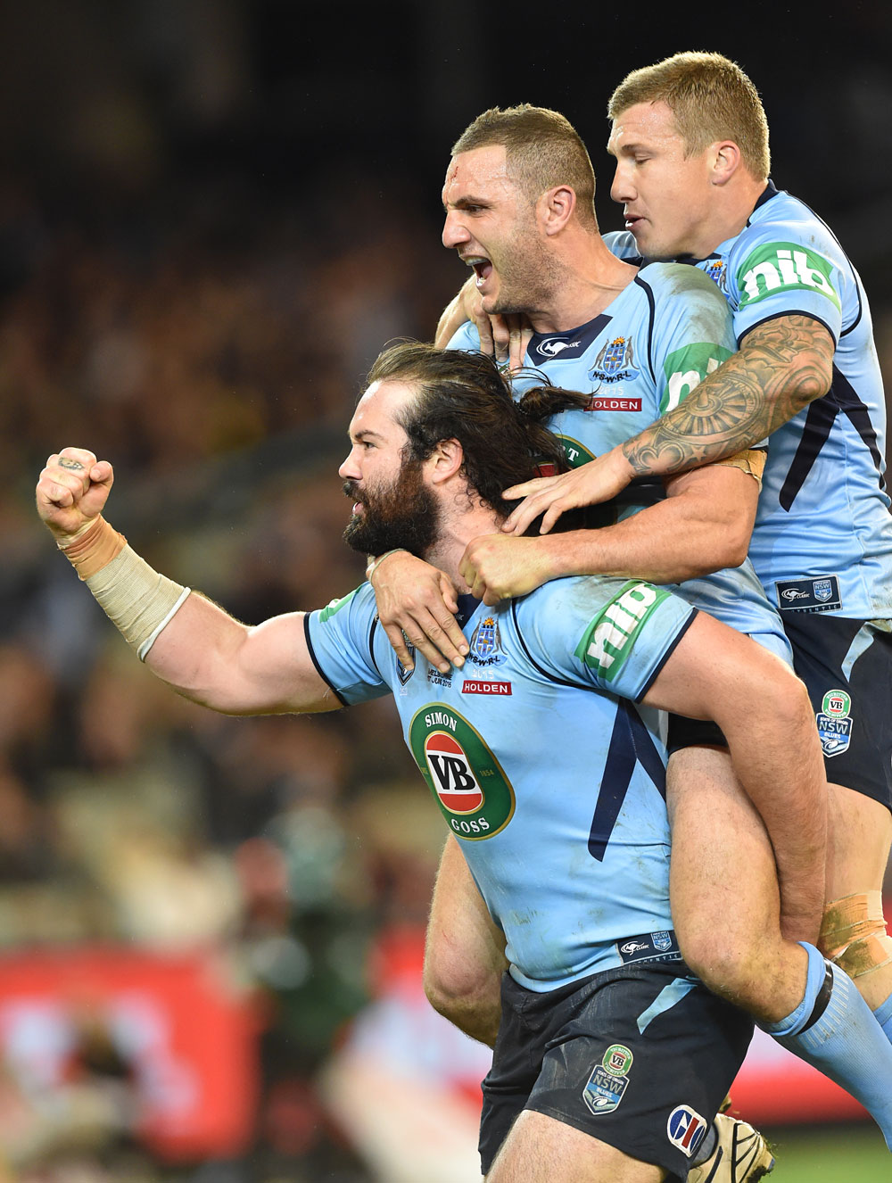 Aaron Woods celebrates a try with teammates