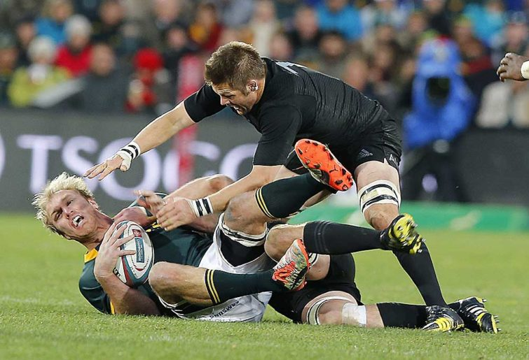 South Africa flanker Schalk Burger (L) is tackled by New Zealand flanker Richie McCaw