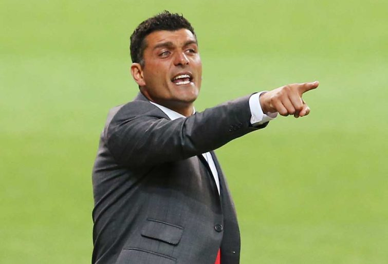 John Aloisi speaks to his players on the sideline