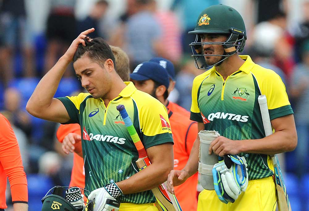Australia's Marcus Stoinis, left, and Australia's Mitchell Starc walk back to the pavilion