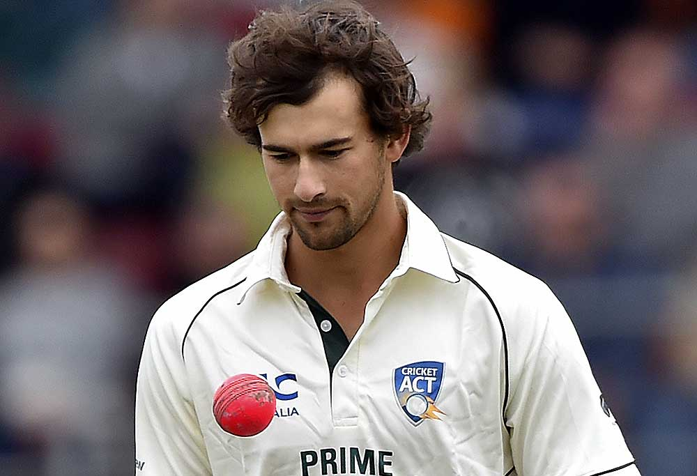 Ashton Agar walks back to his bowling mark with a pink ball