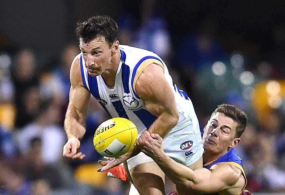 Brent Harvey of North Melbourne is tackled by Dayne Zorko