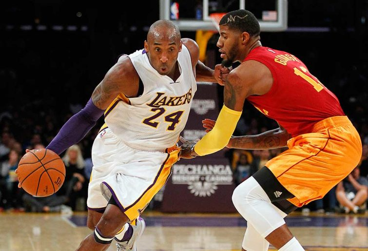 Los Angeles Lakers forward Kobe Bryant drives past Indiana Pacers forward Paul George
