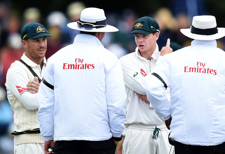 Australian captain Steve Smith gestures with umpires