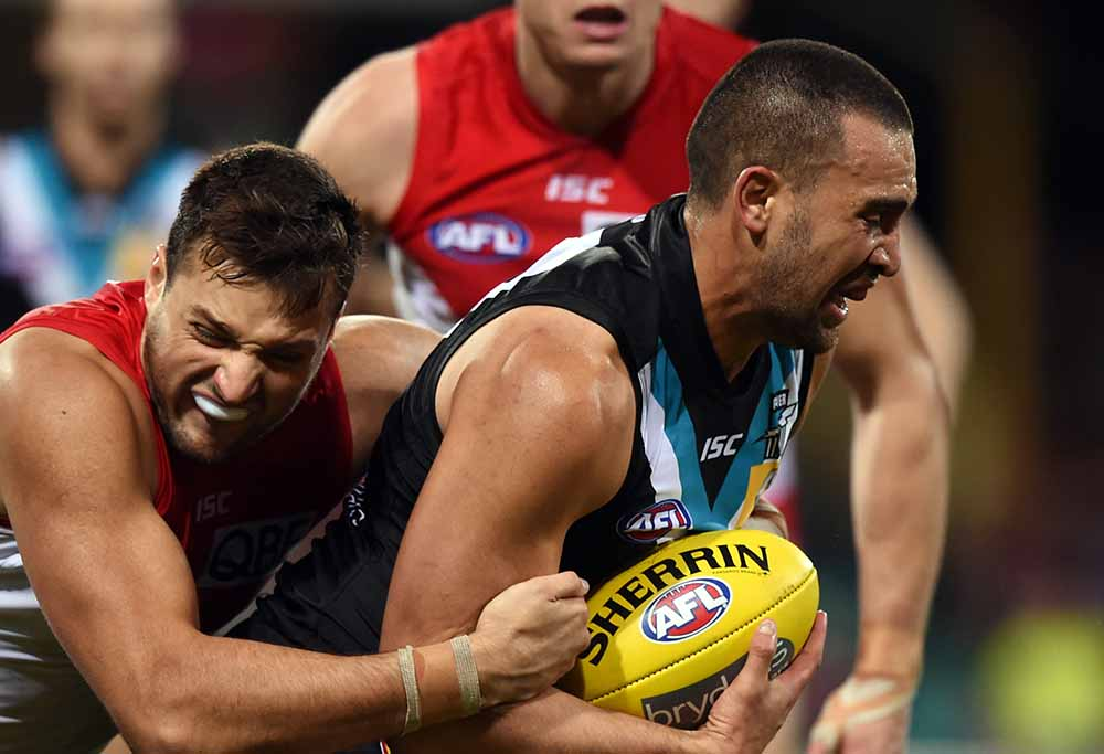 Travis Boak of the Port Adelaide Power is tackled by Toby Nankervis of the  Sydney Swans