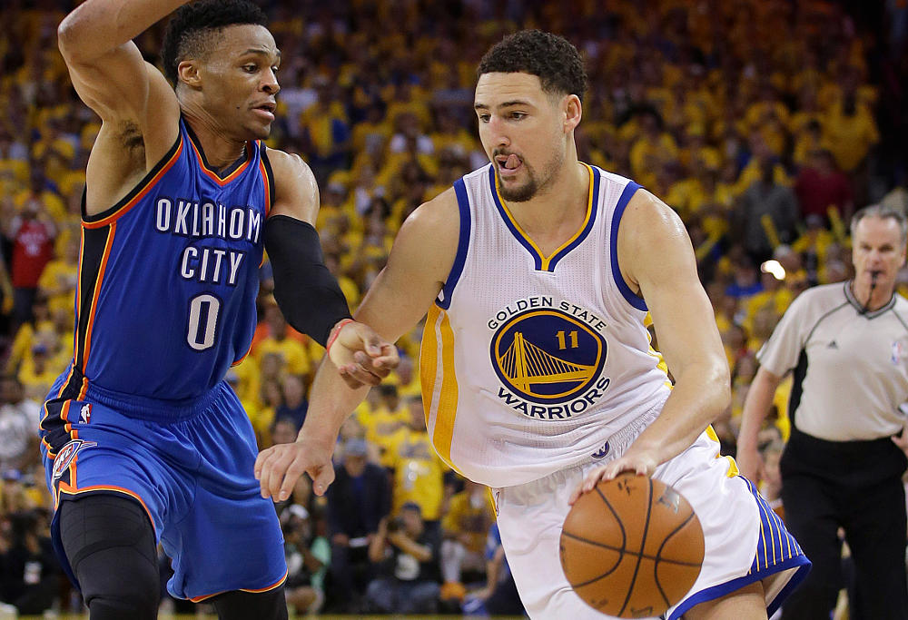 Klay Thompson dribbles past Russell Westbrook