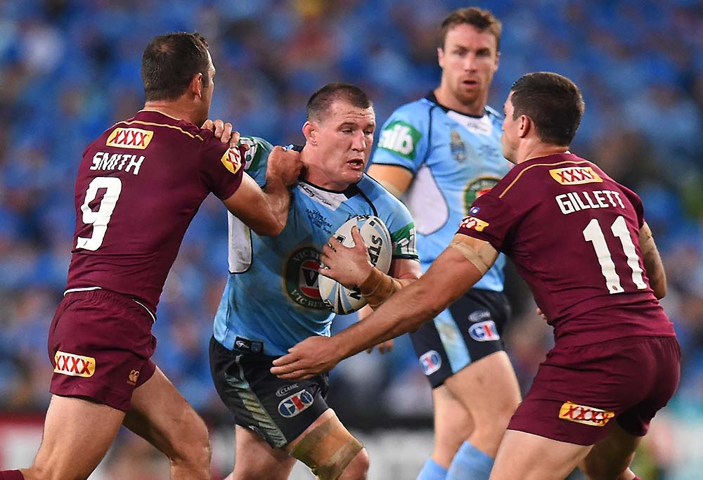 Paul Gallen of the Blues is tackled by Cameron Smith and Matthew Gillett of the Maroons