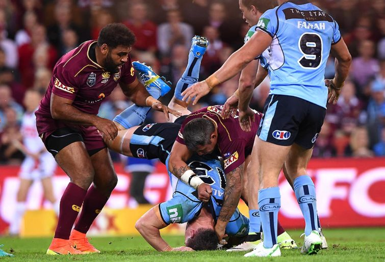 NSW captain Paul Gallen is spear tackled by Queensland's Sam Thaiday and Corey Parker