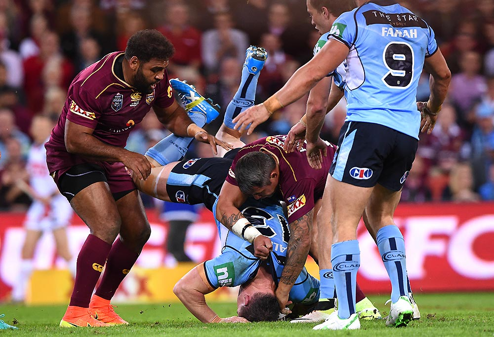 NSW captain Paul Gallan is spear tackled by Queenslands Sam Thaiday and Corey Parker