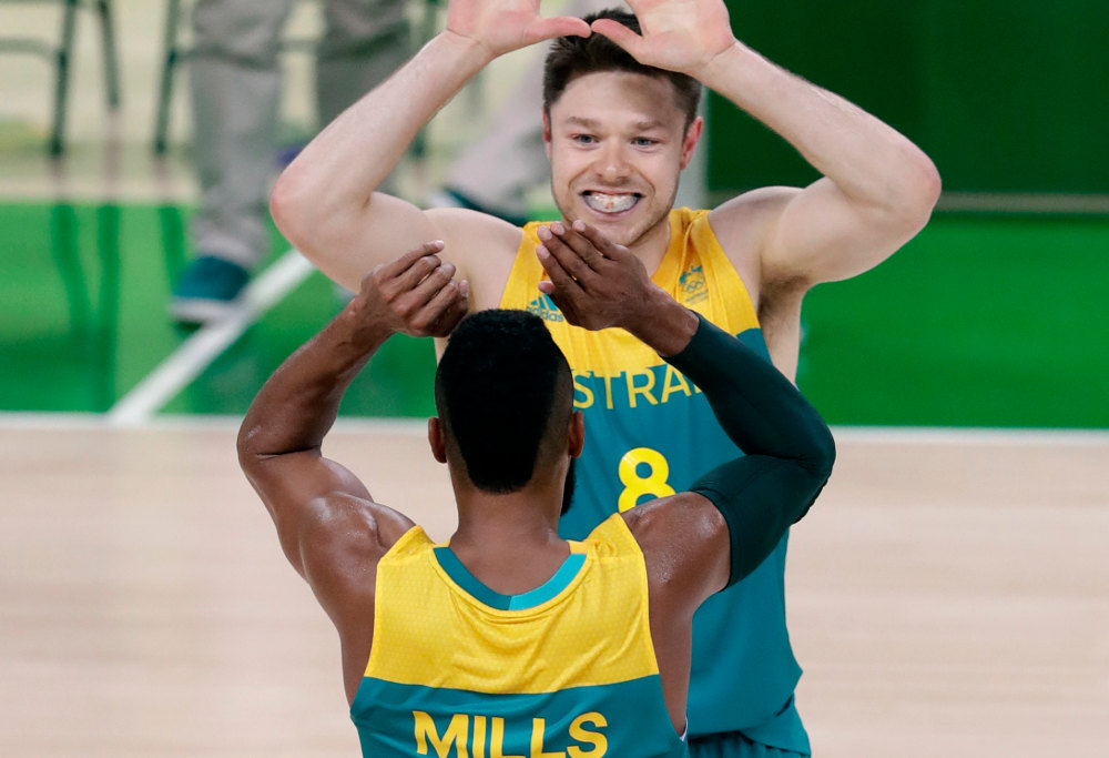 Patty Mills and Matthew Dellavedova high five during the Boomers win over Serbia.