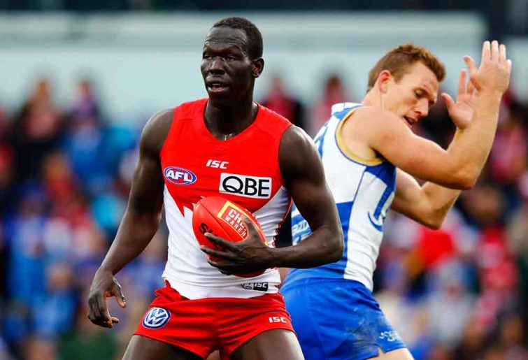 Aliir Aliir of the Sydney Swans bumps a North Melbourne Kangaroos player
