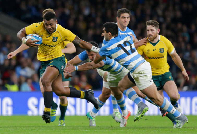 Australia's Samu Kerevi, left, fends off the tackle of Argentina's Jeronimo De La Fuente