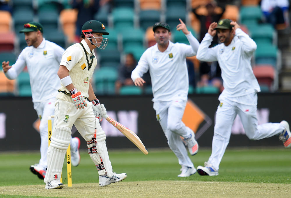 South Africa's teammates celebrate the wicket of Australia's David Warner