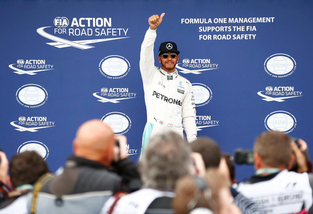 Mercedes Formula One driver Lewis Hamilton gives a crowd of photographers the thumbs up.
