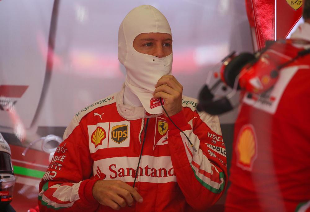 Sebastian Vettel takes a breather in the Ferrari garage during Austrian Grand Prix qualifying.