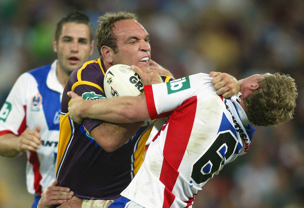 Gorden Tallis of the Broncos fends off the tackle of Steven Witt of the Knights